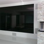 Fernsehwand aus schwarz lackiertem Glas mit Durchsicht für Fernsehbild